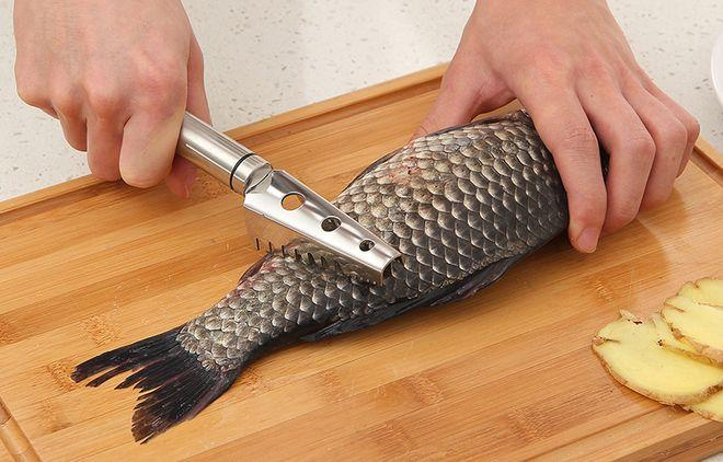 Чистка рыбы на разделочной доске специальным ножом