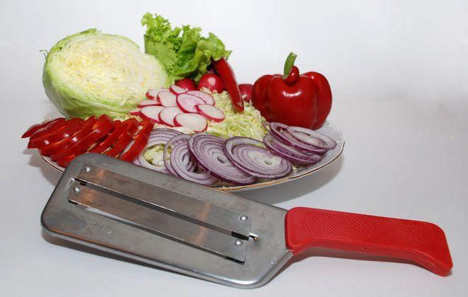 Нож для шинковки капусты на фоне нарезанных овощей