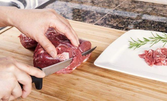 Обвалочным ножом режут мясо на доске
