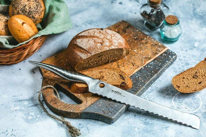 Хлебный нож с волнистым лезвием на фоне хлеба
